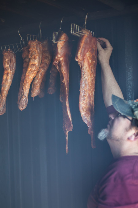 Jean Duos in his smokehouse prepping a classic Cajun recipe ingredient for Smoked Turkey Neck Gumbo..